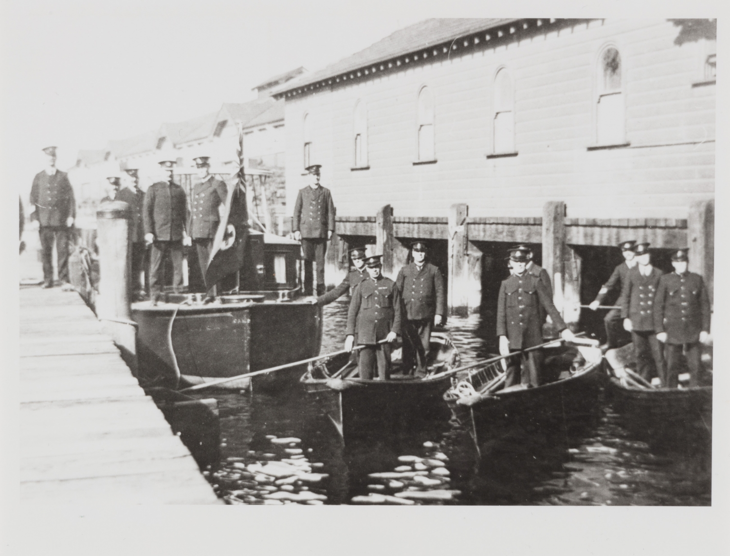 Policemen on set of four boats, one larger motorboat, three smaller rowboats