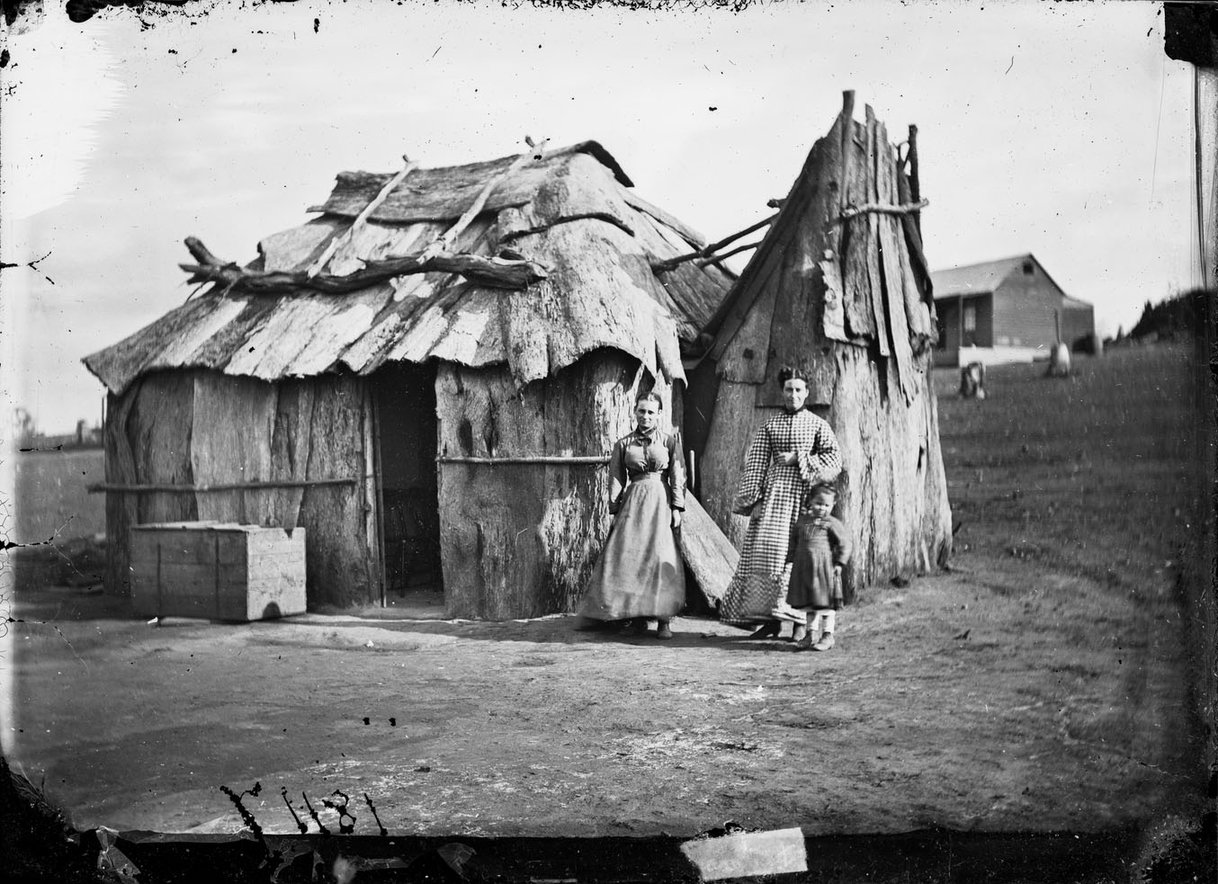 B/W photo of pioneering women standing outside roughly built bark covered cottage on gold fields