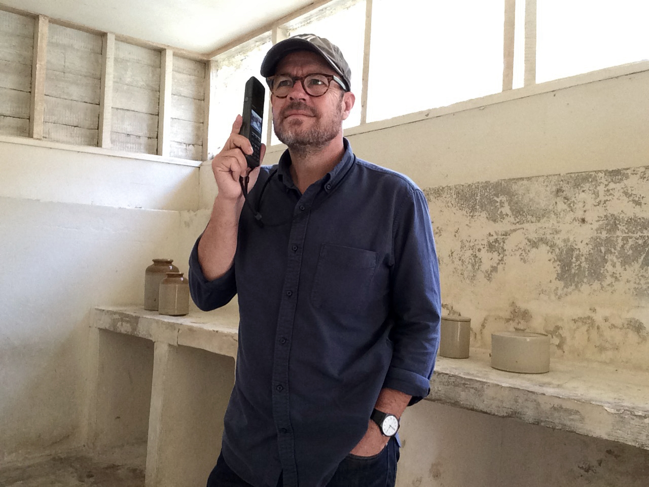 Man hold audio tour handset to his ear in a sparce and white painted dairy