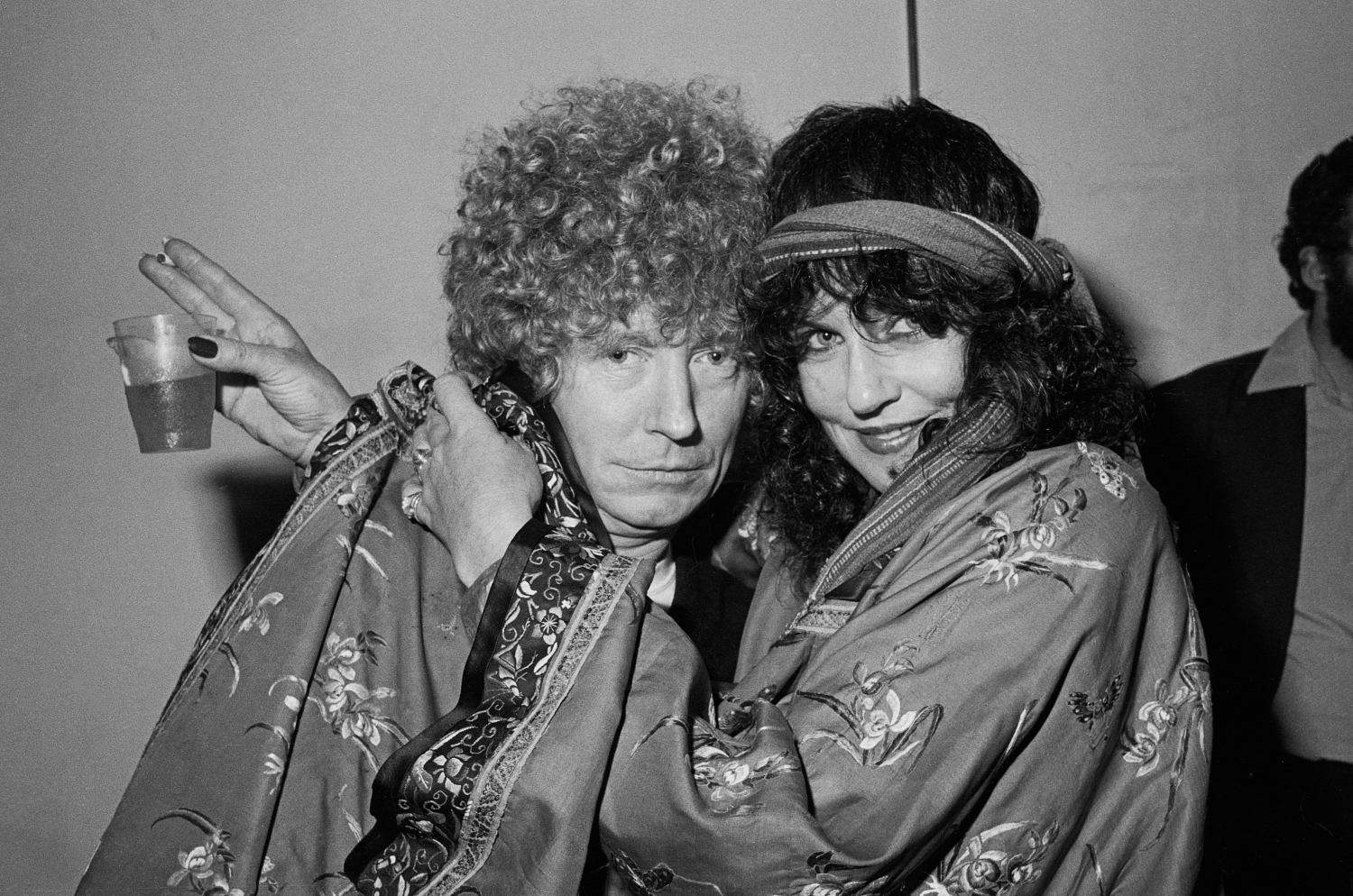 Man with curly hair being hugged by woman with headscarf holding drink and cigarette.