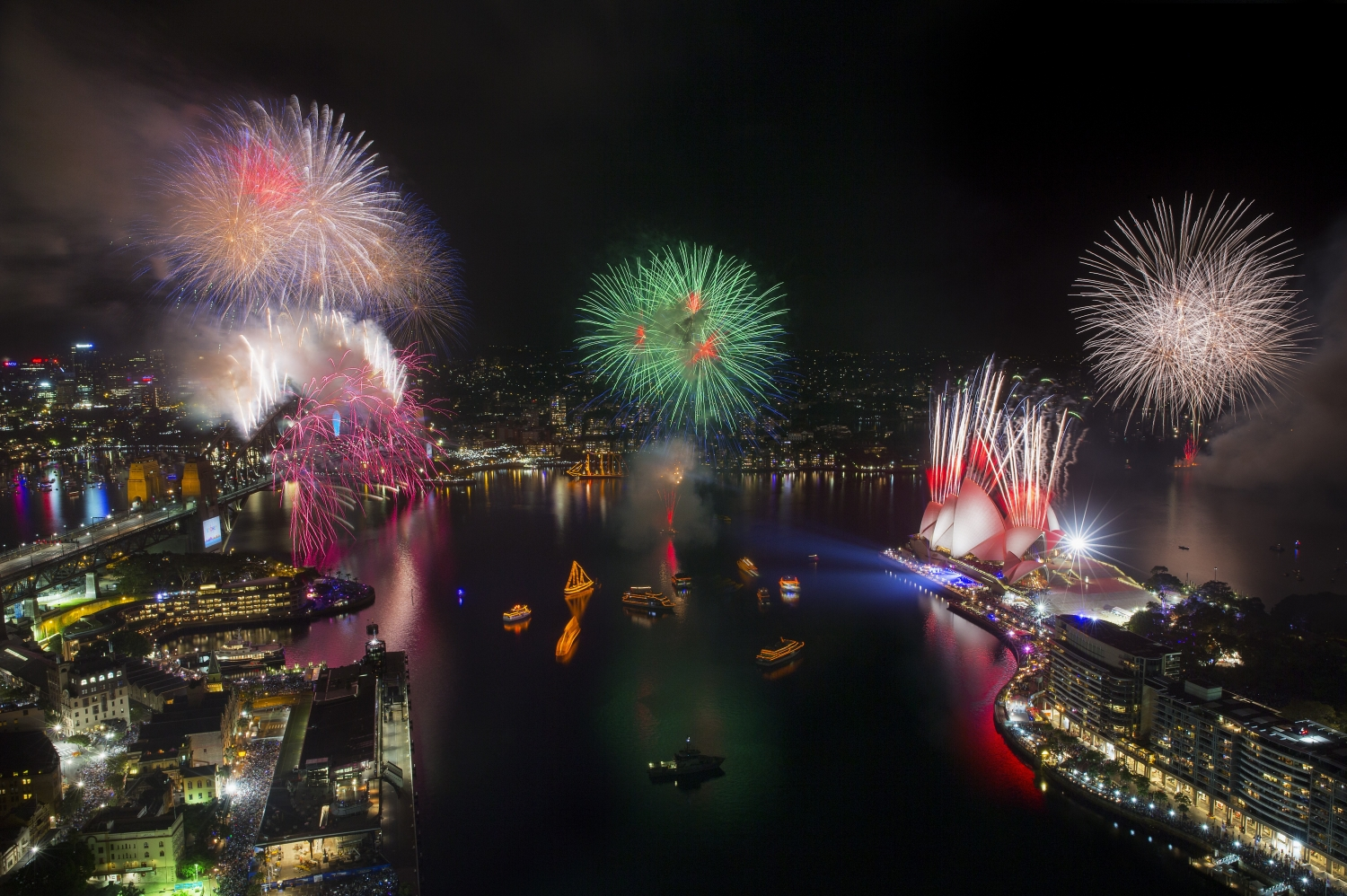 Brightly coloured fireworks explode above the water of Circular Quay and the Sydney Harbour Bridge while revelers crowd the streets of Sydney's Rocks area to celebrate New Years Eve.
