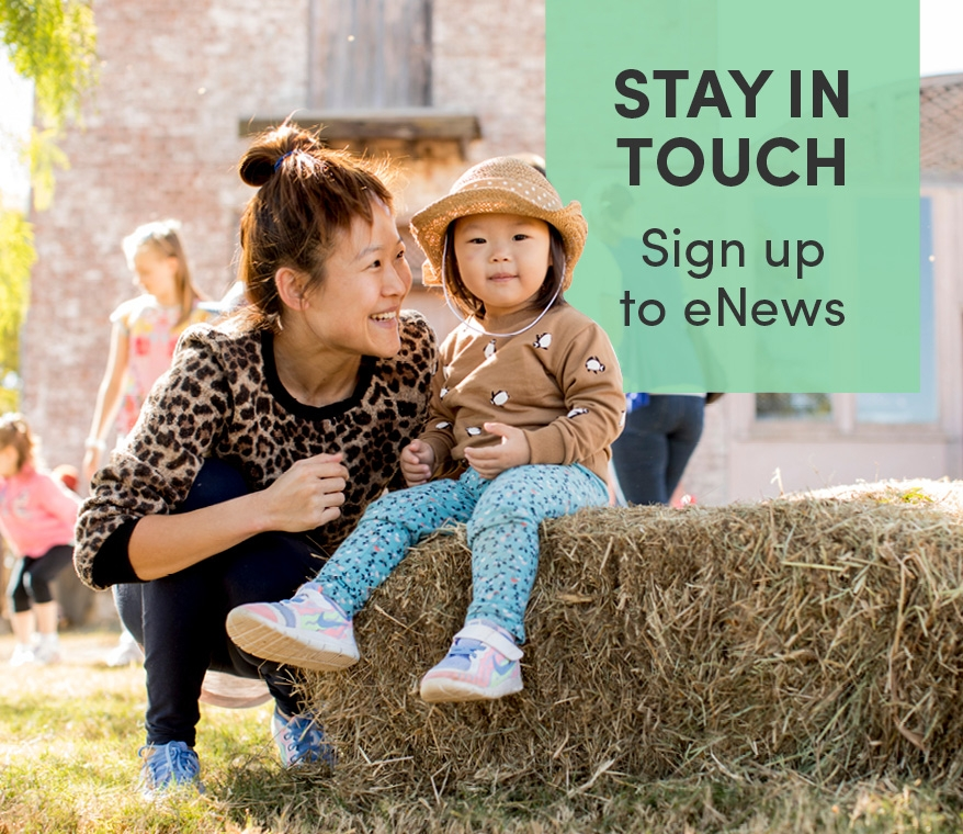 Woman with child seated on hay bale in out door setting. Promotion of eNews signup.
