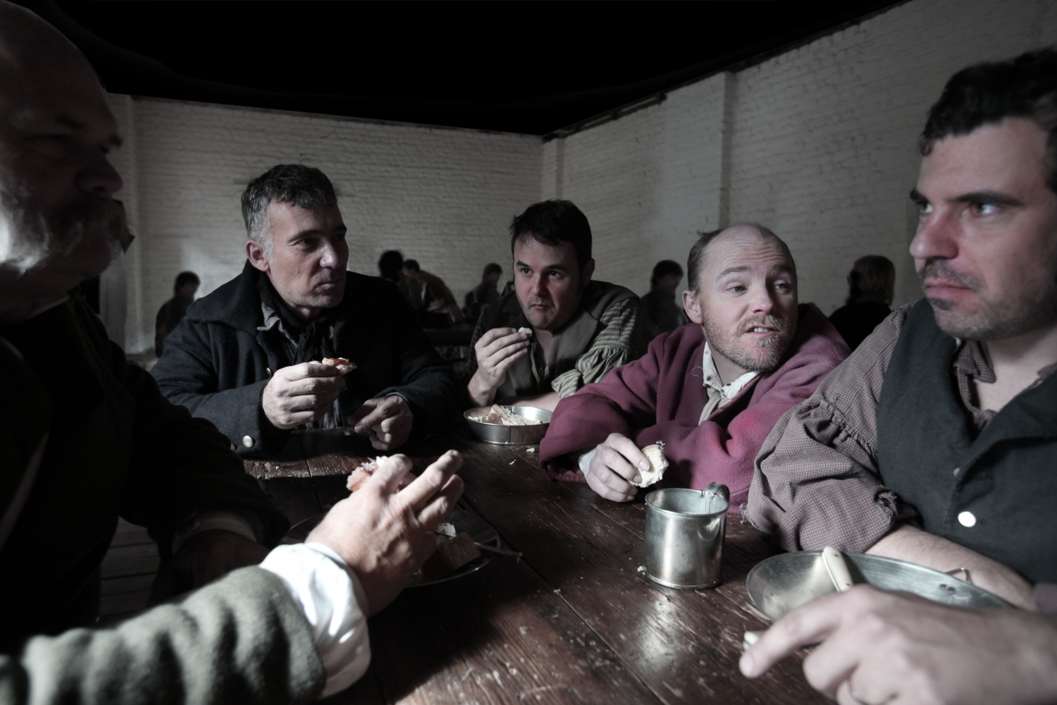 Moody image of men sitting eating food from tin plates.