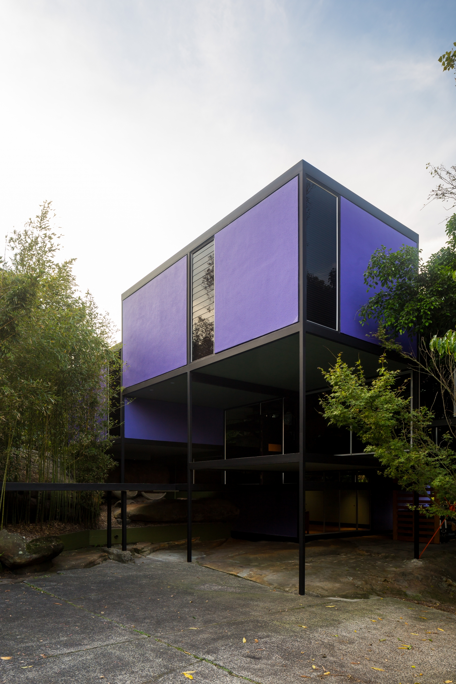 View of a house with large purple panels and tall, slim windows.