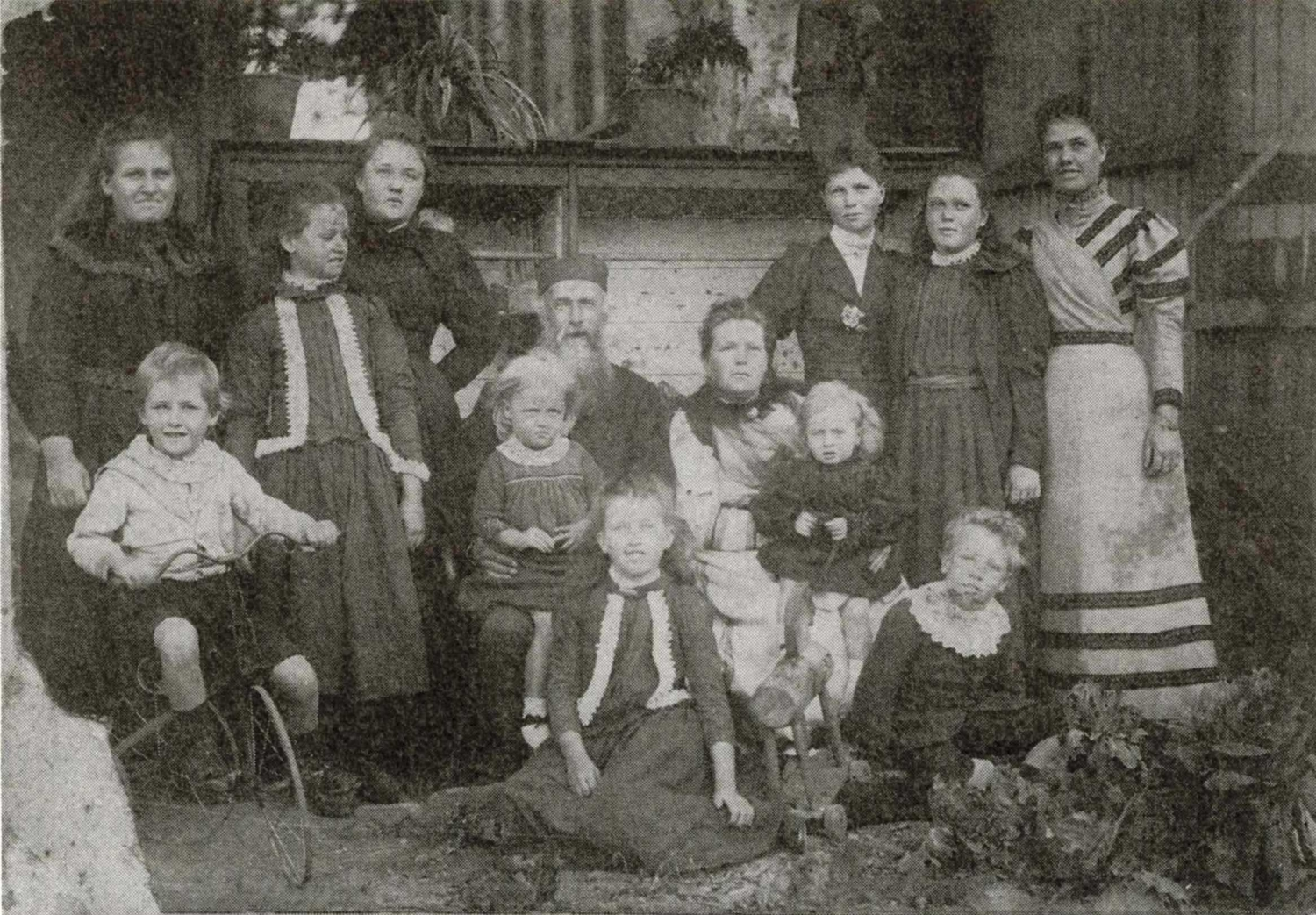 B/W photo of a group of people including young children, teenagers and elderly parents.