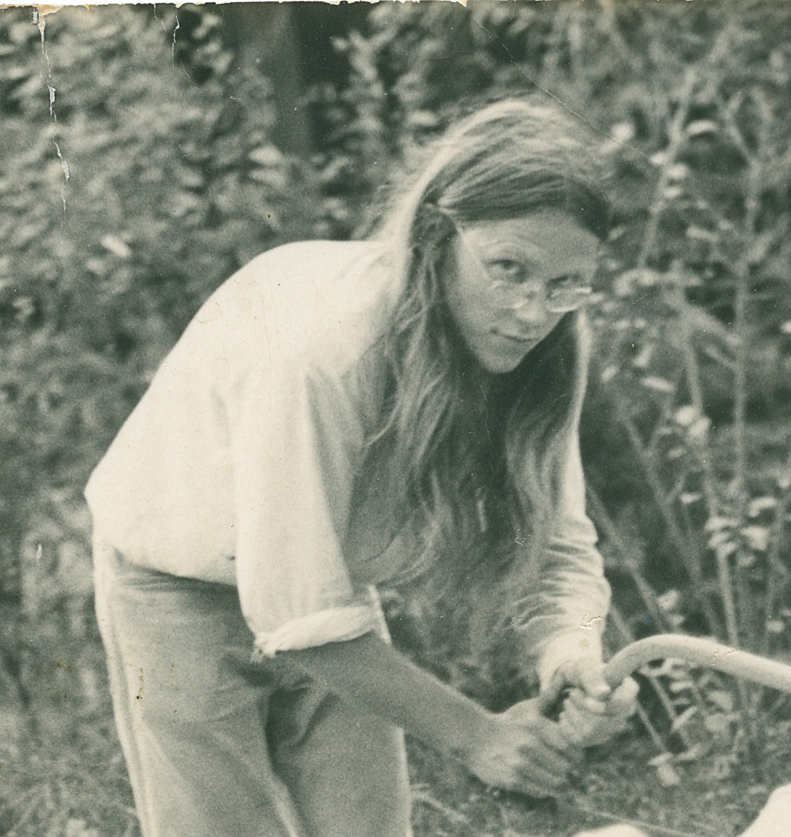 Black and white photo of young man using saw in garden setting.