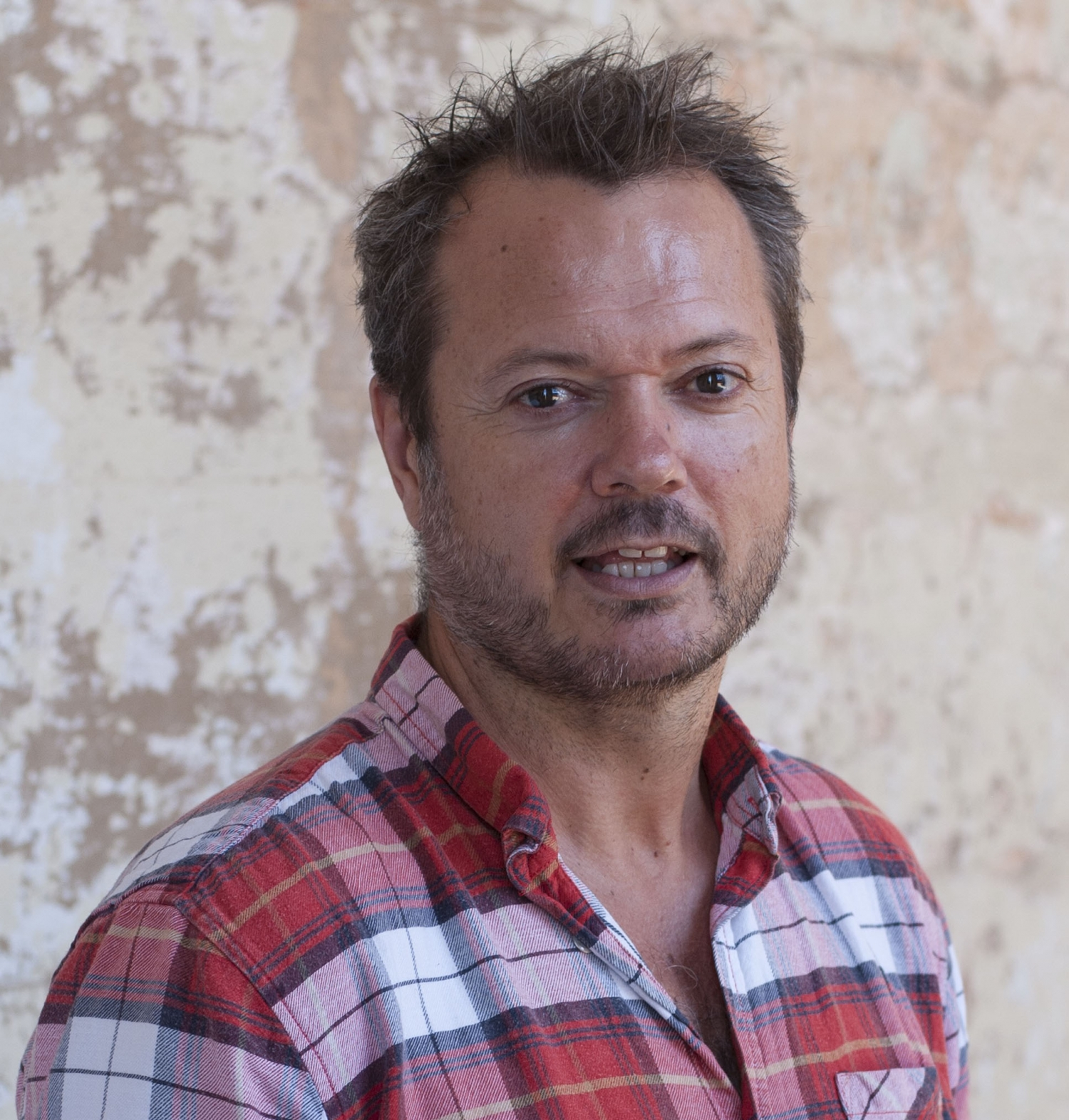 Headshot of a man in a chequered shirt