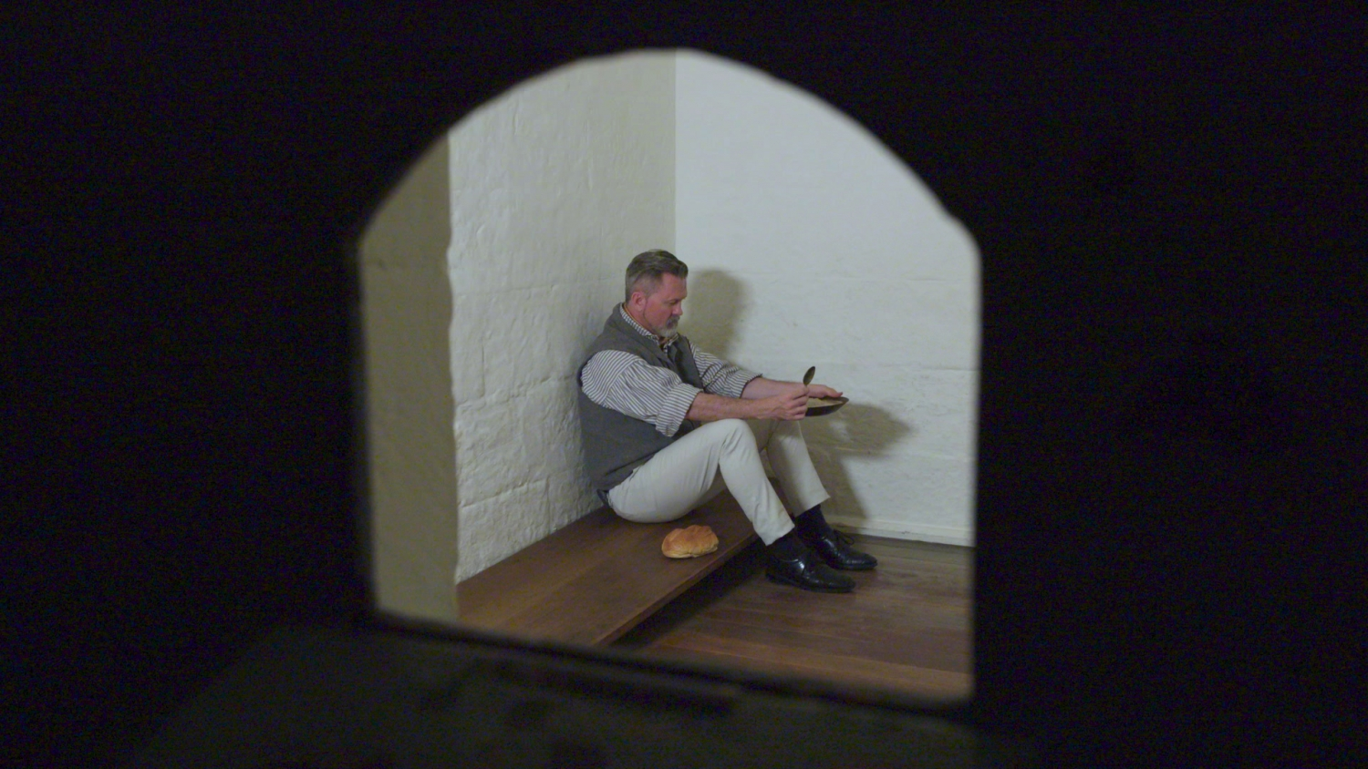 An actor dressed as Captain Moonlite languishes in a police holding cell.