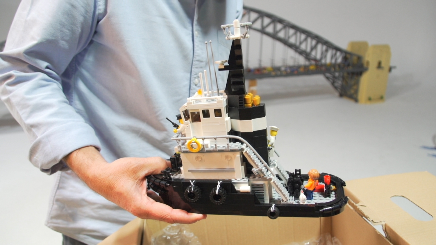 Colourful model of tugboat built out with Lego with minifig passengers and tyre bumpers