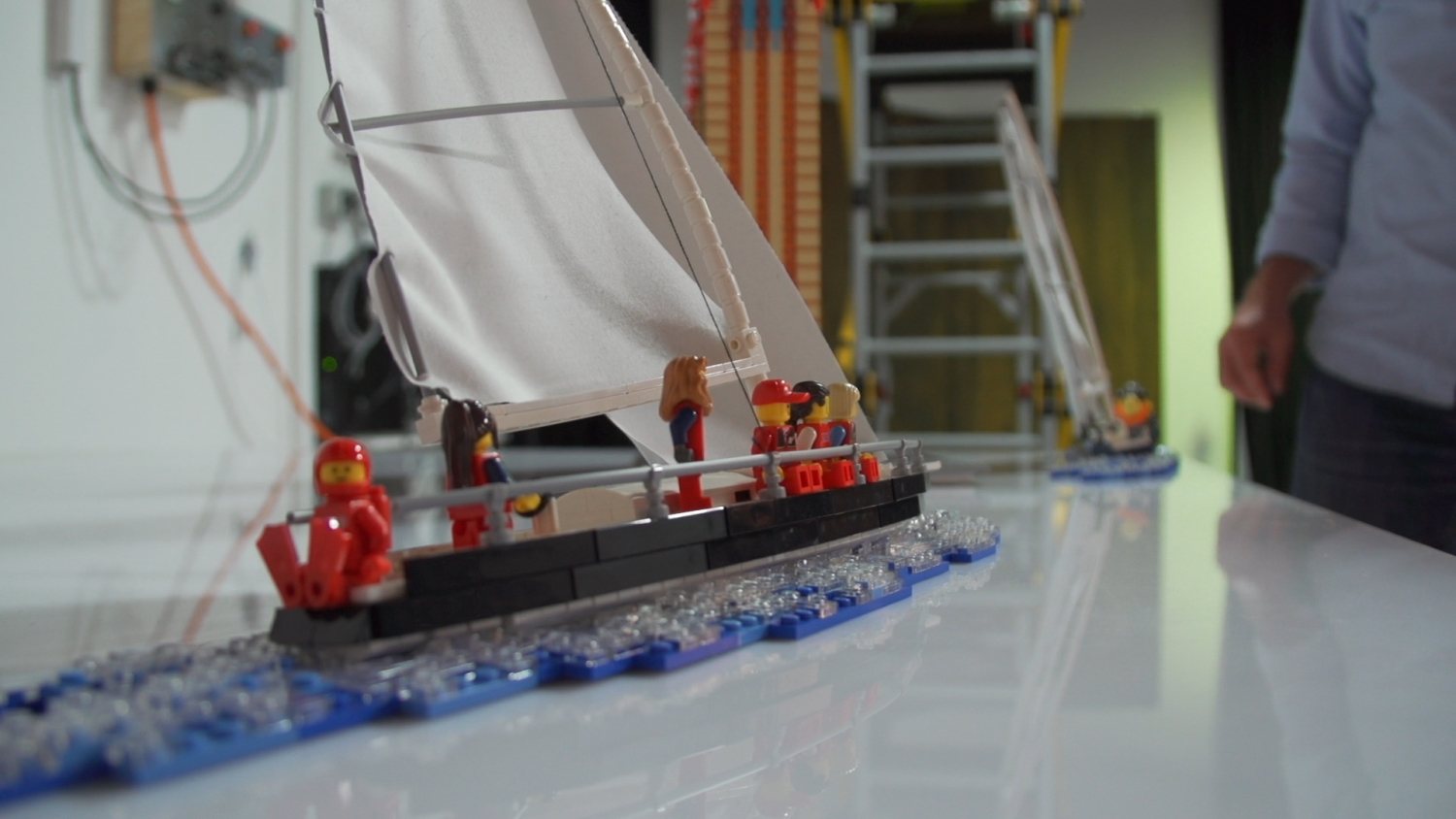 Colourful model of racing yacht under sail built in LEGO with minifig sailors on board