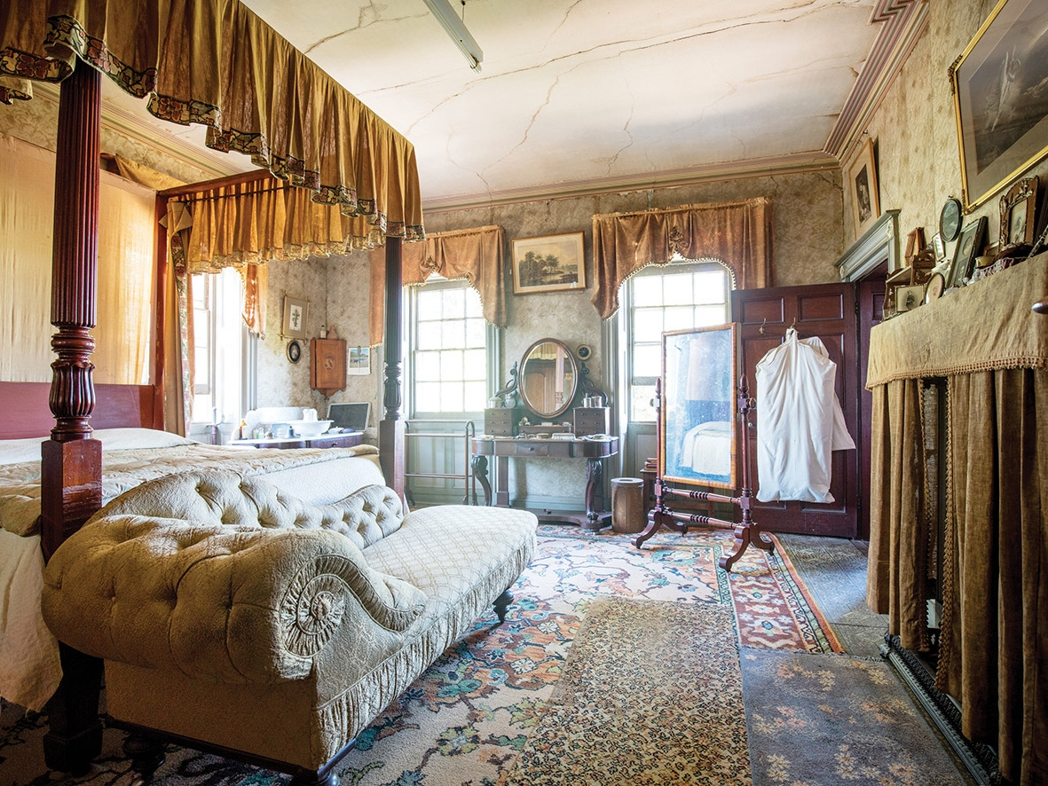Ornately furnished bedroom with canopied bed and chaise longue to left and windows behind.
