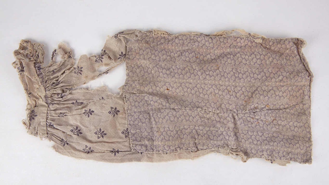 Worn piece of cloth with pattern.