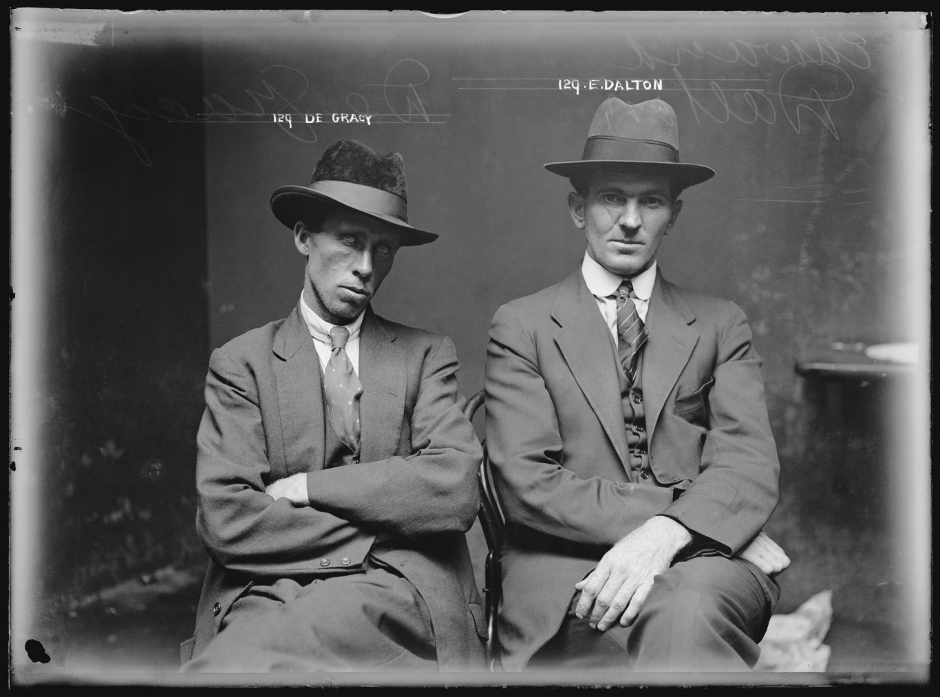 Black and white mugshot of two seated men with hats on.