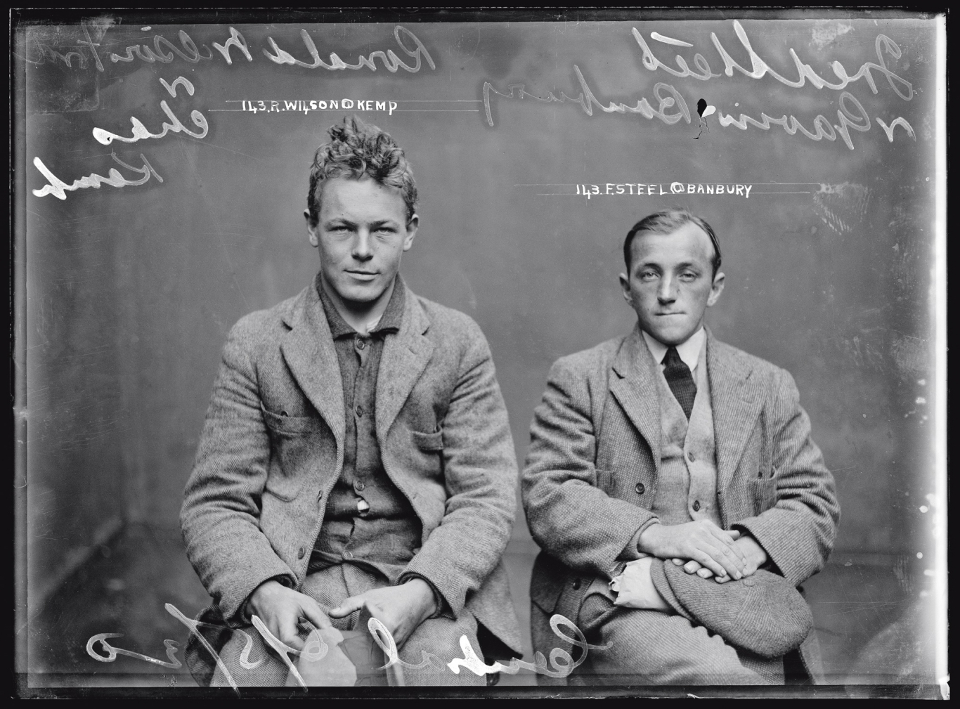 Black and white mugshot of two seated men.