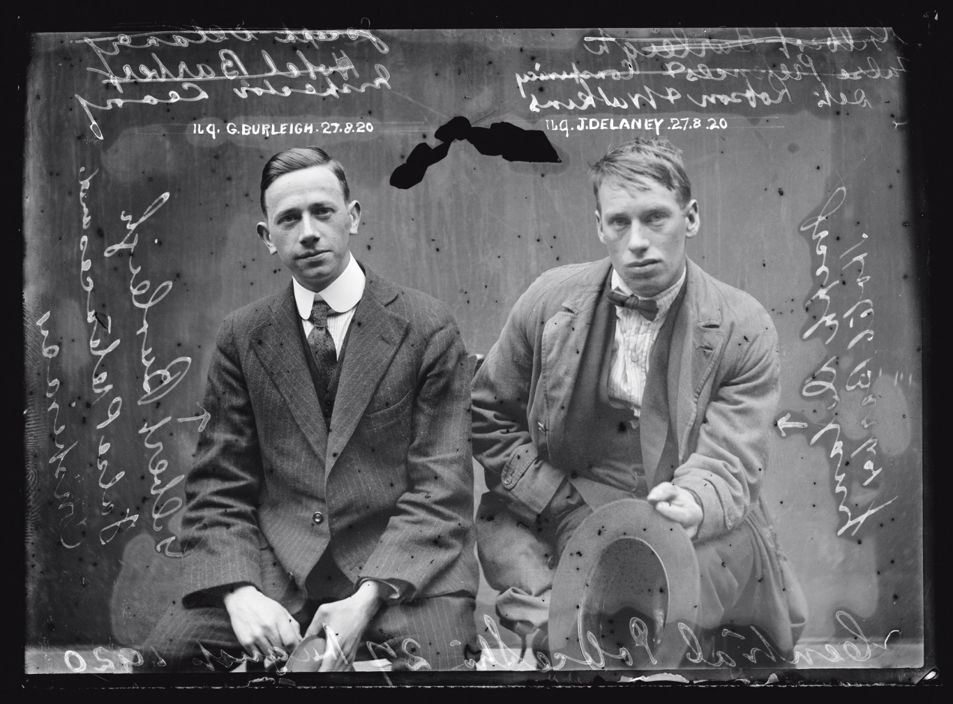 Black and white mugshot of two seated men with inscription marked onto photograph above each man.