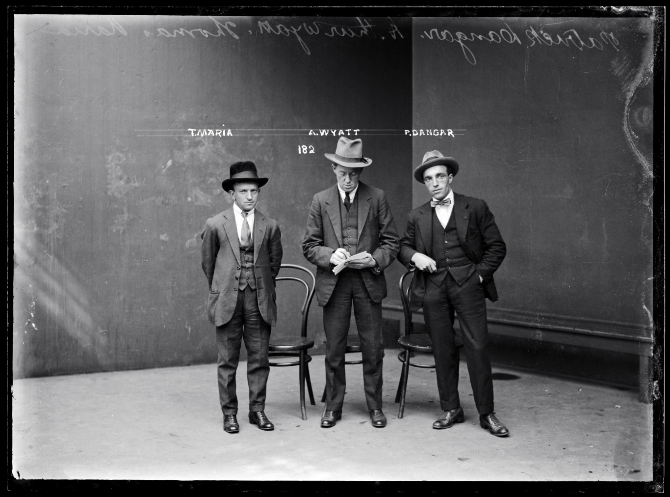 Black and white mugshot of three standing men.
