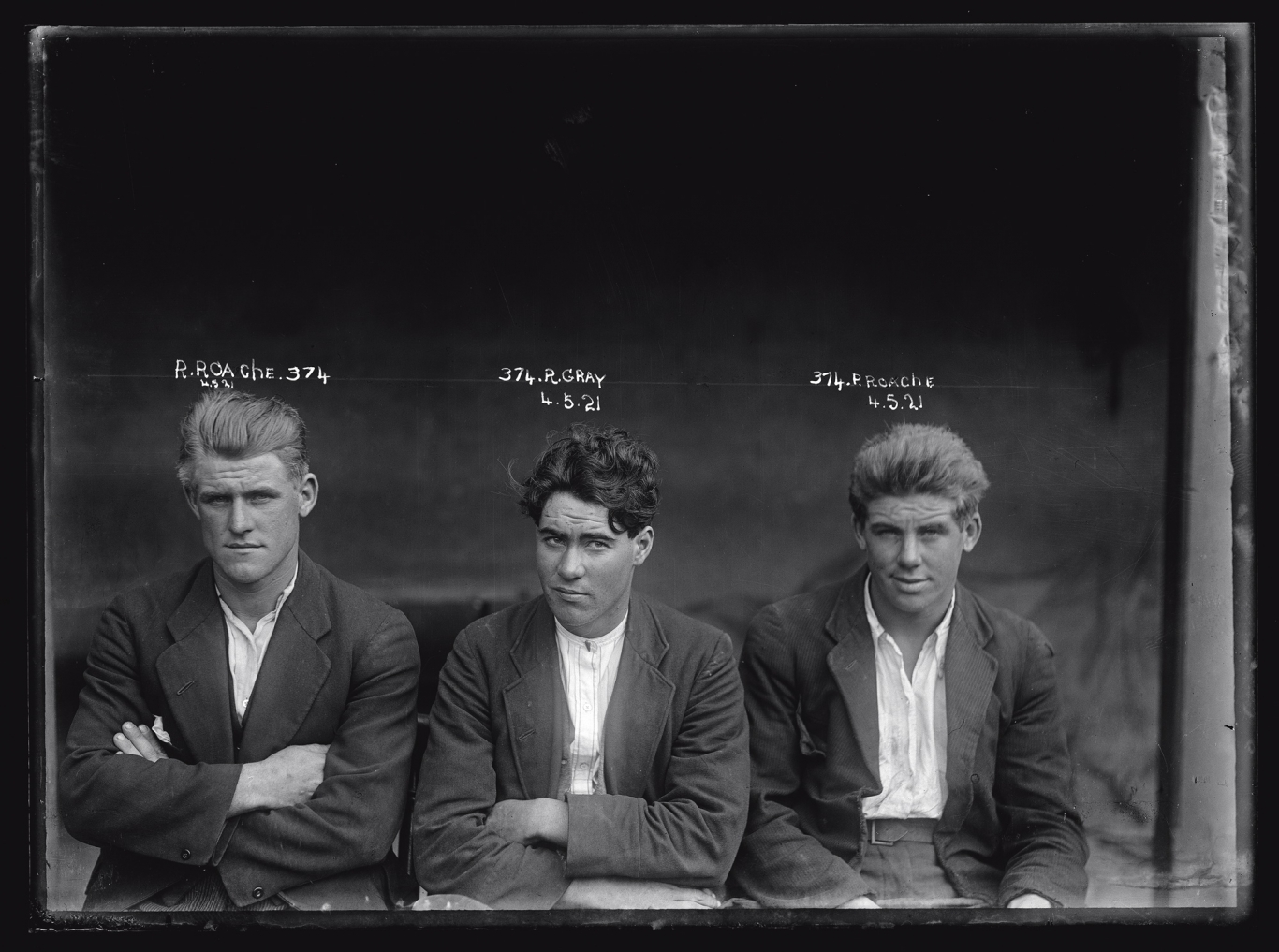 Black and white mugshot of three seated men.