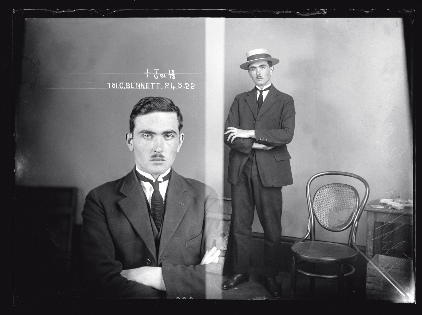 Black and white dual mugshot. Man, seated on left, standing with hat on, on right.