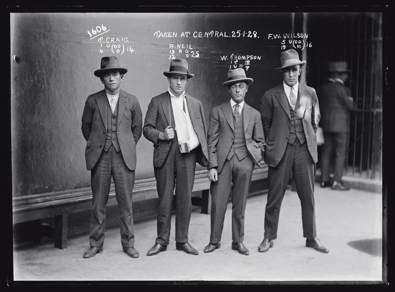 Black and white mugshot of four men standing with hats on.