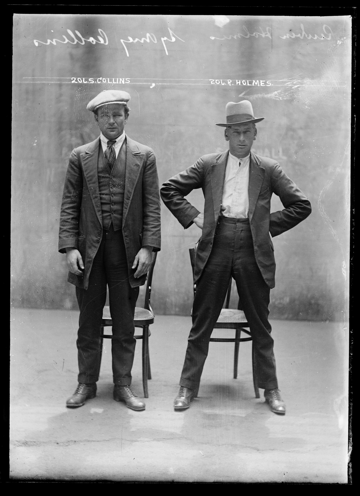 Black and white mugshot of two standing men.