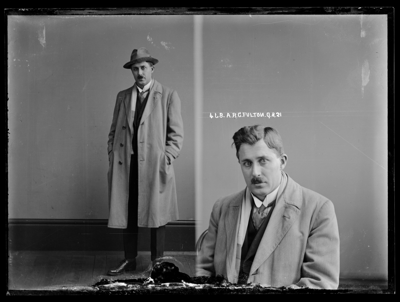 Dual black and white mugshot, man standing with hat on (left) and seated (right).