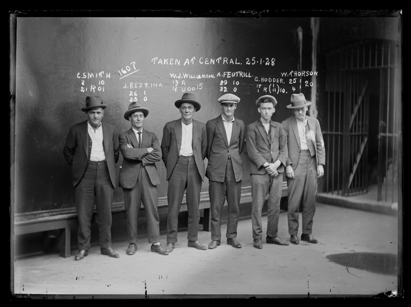 Black and white mugshot of six men standing in line, all with hats on.