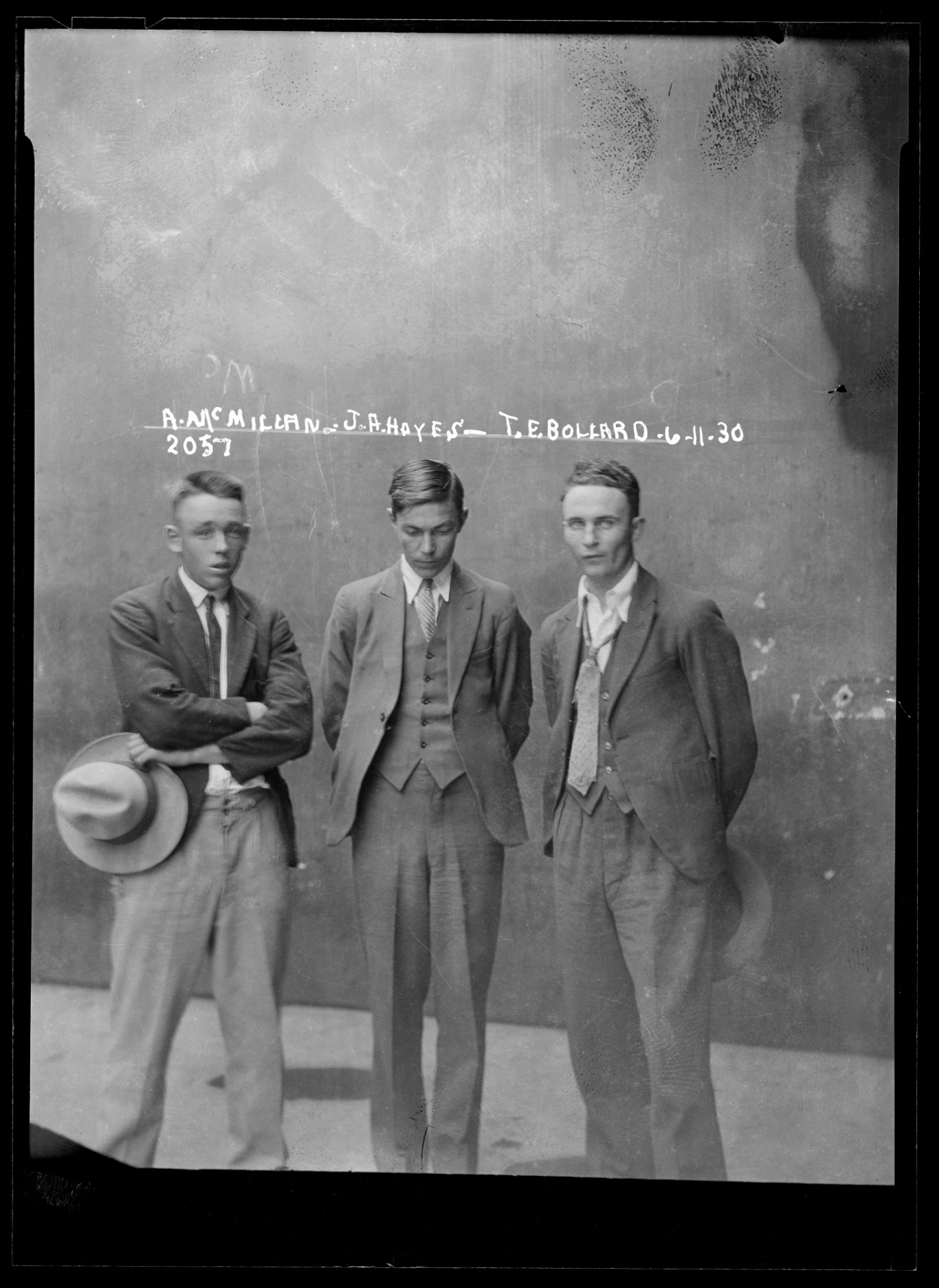 Mugshot of three men standing.