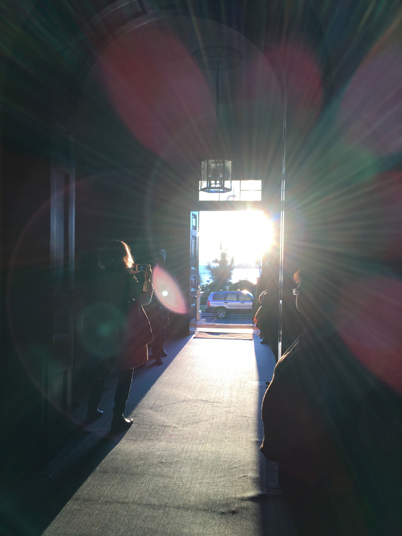 Looking down hallway and out of open front door with sunrise light streaming directly in.