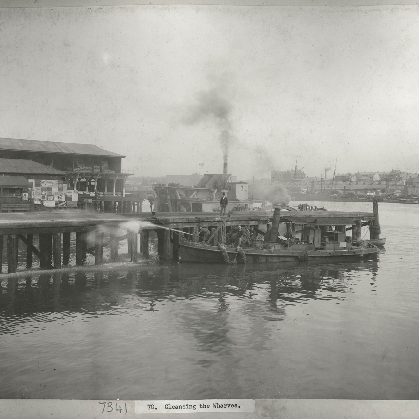 Black and white photograph looking across water to wharves with smoke in distance.