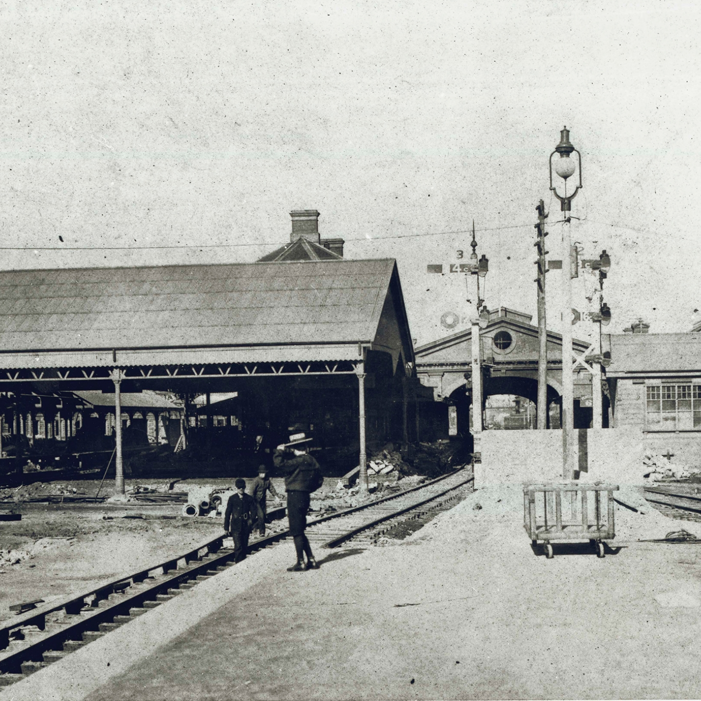 Black and white view of tracks leading into station buildings.