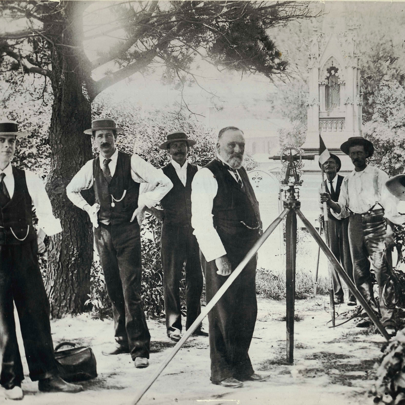 Black and white photo of group of men in shirtsleeves and waistcoats in outdoor setting.