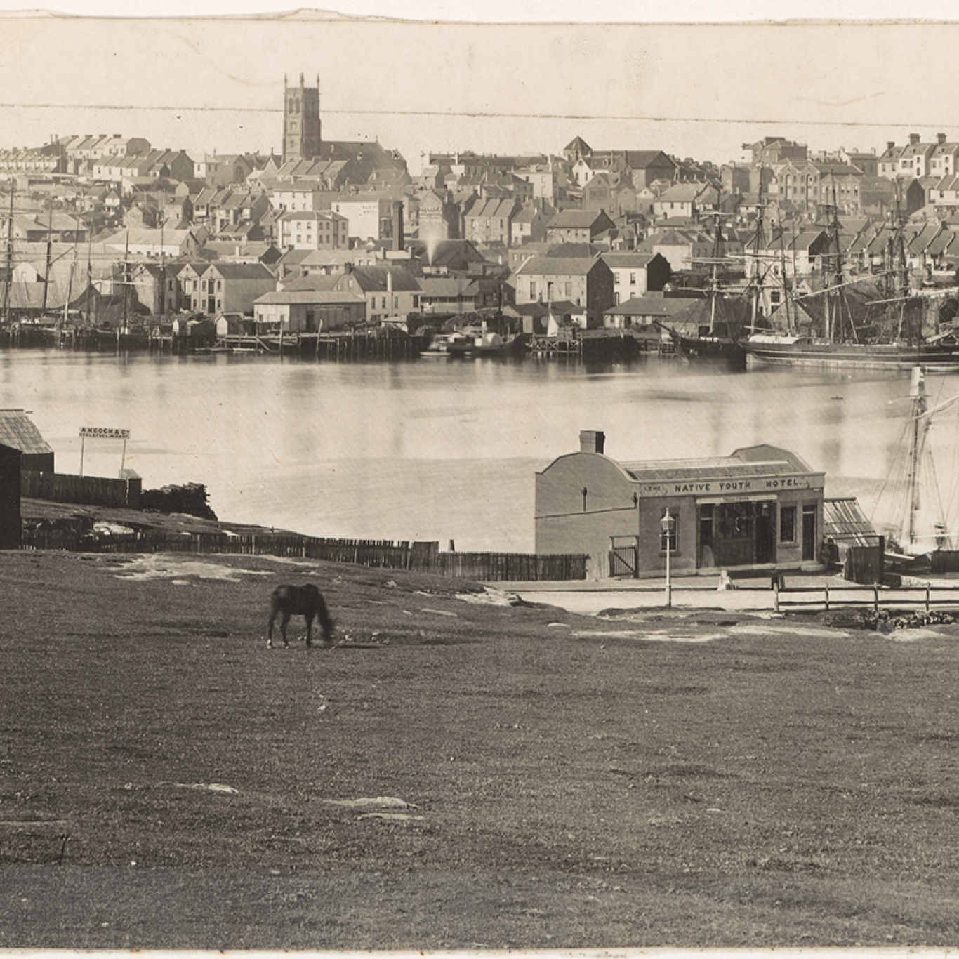 Black and white photograph of forreshore area with buildings across water.