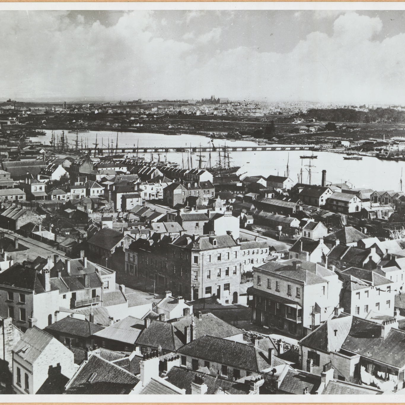 Black and white photograph looking down across buildings to water in middle distance.