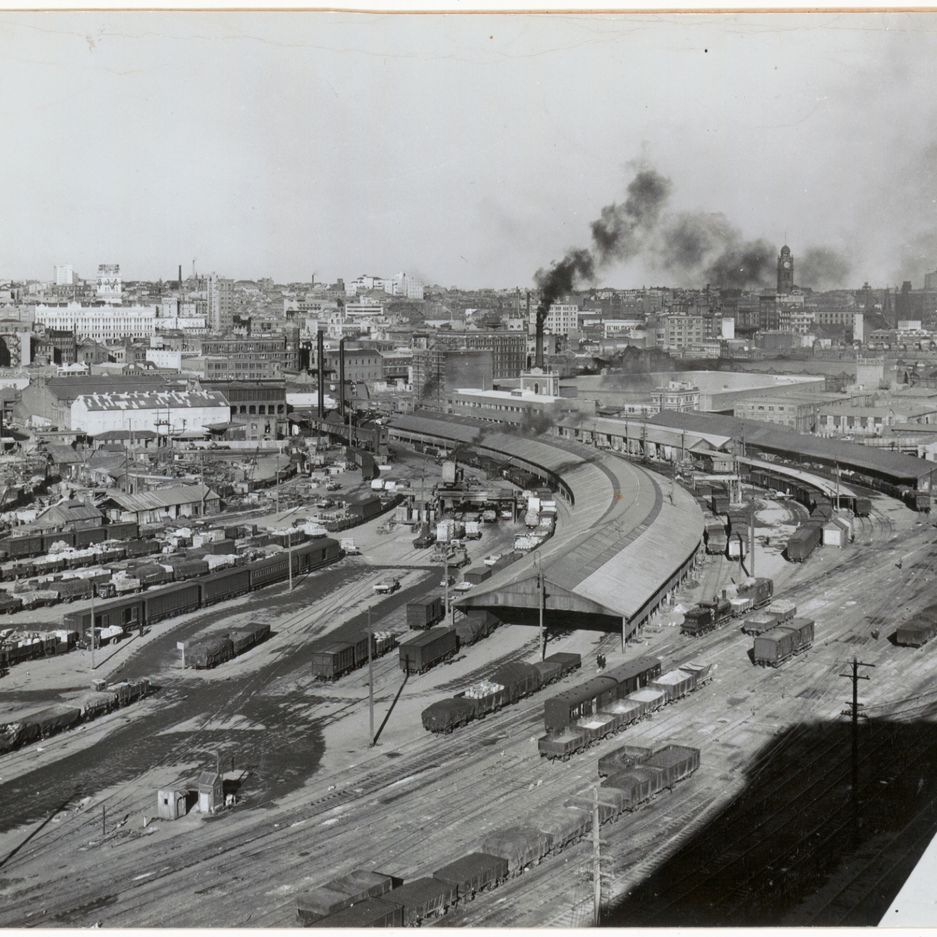 Black and white photograph looking across goods yard with smoke on horizon.