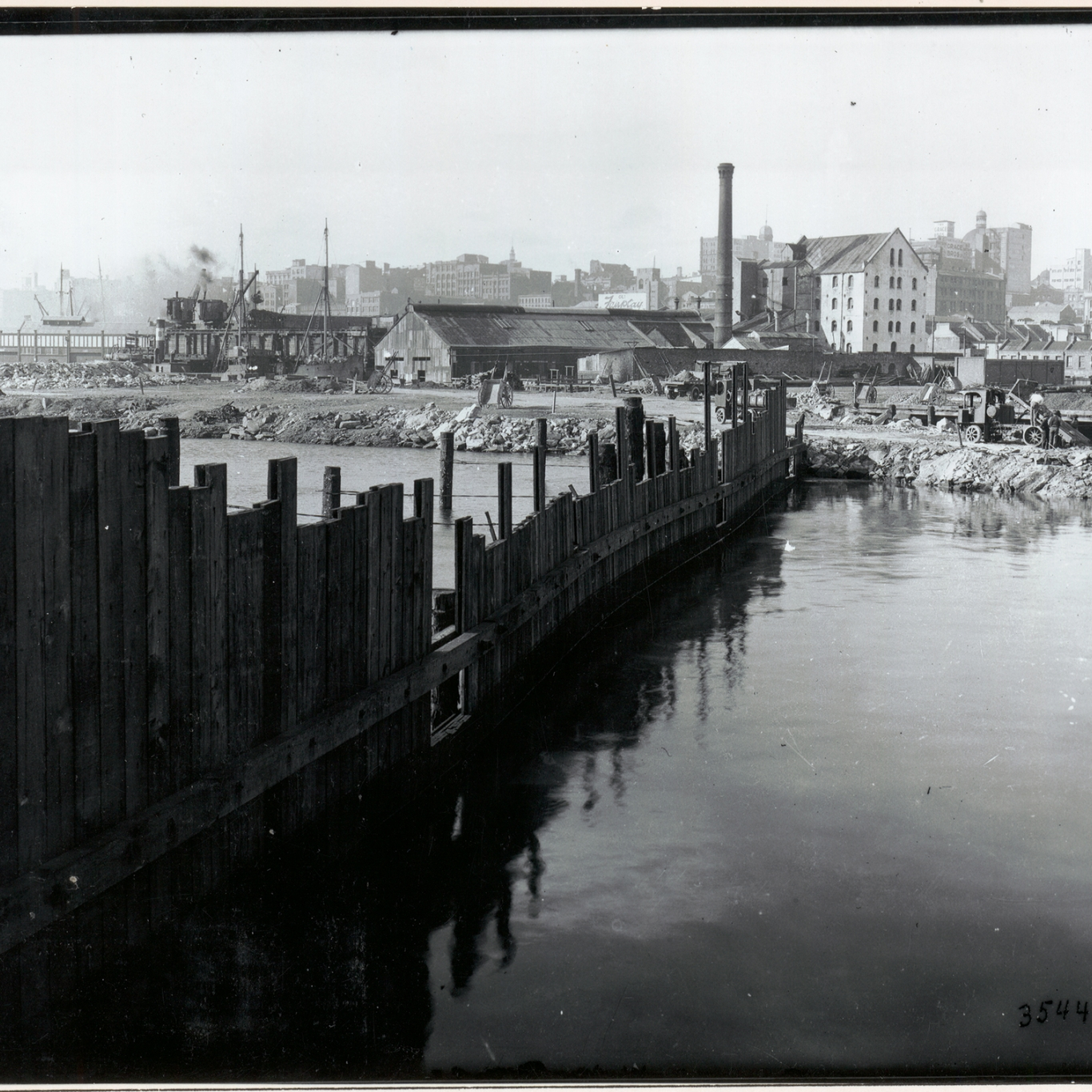 Black and white photograph of fenceline going into water and industrial area beyond.