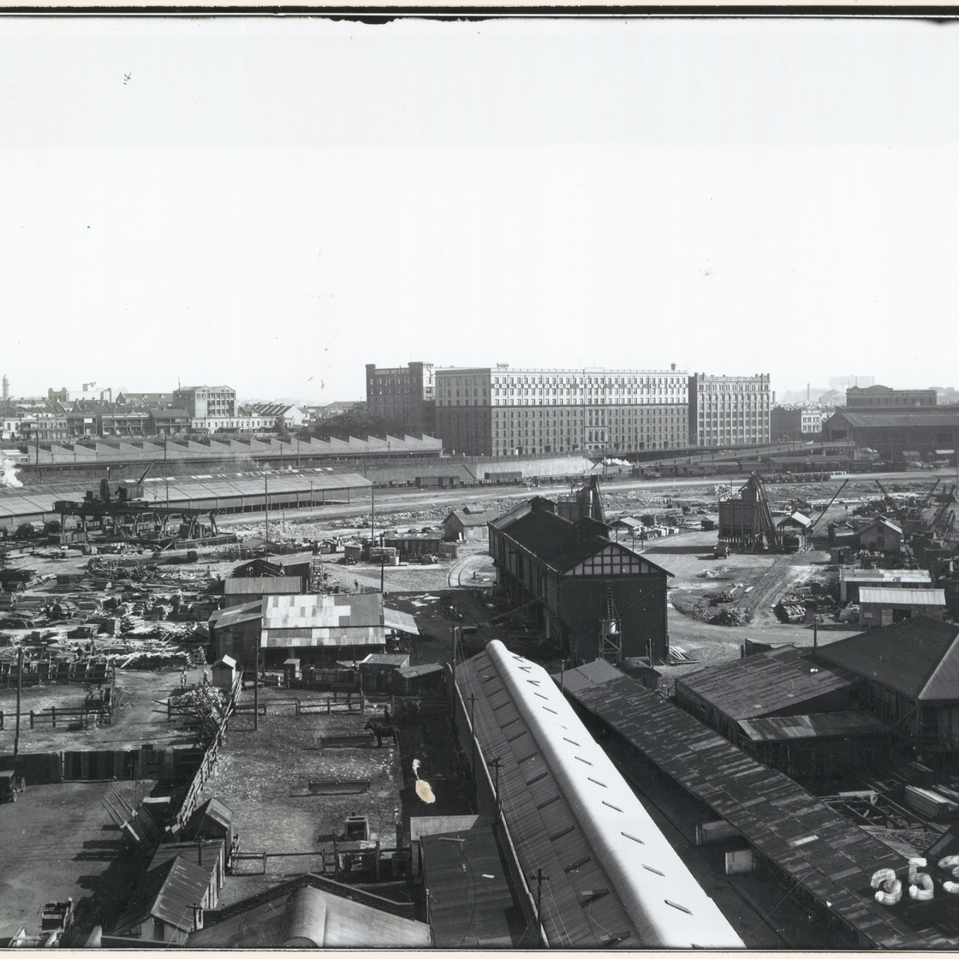 Black and white photograph looking over rooflines.