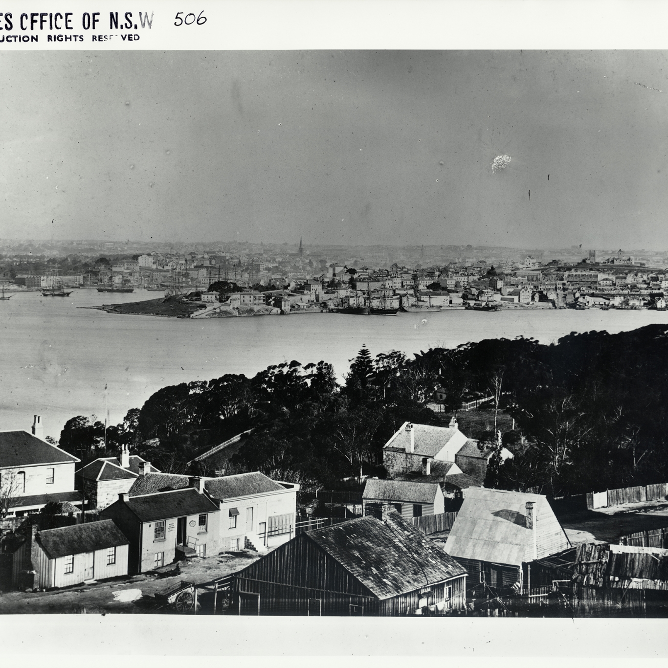 Black and white photograph looking across water with buildings and vegetation in foreground.