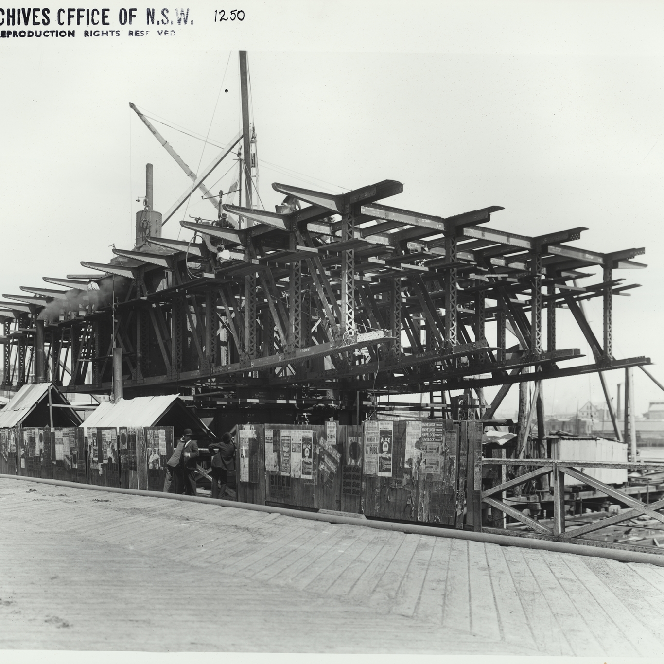 Black and white photograph of partially built bridge with cranes and scaffolding.