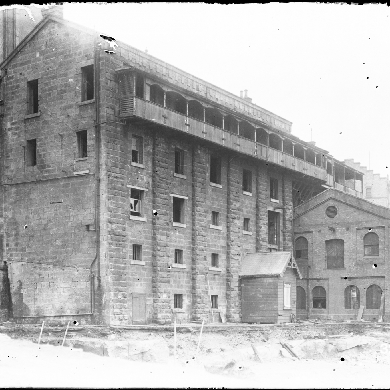 Black and white photograph of multistorey building with covered verandah along top floor.