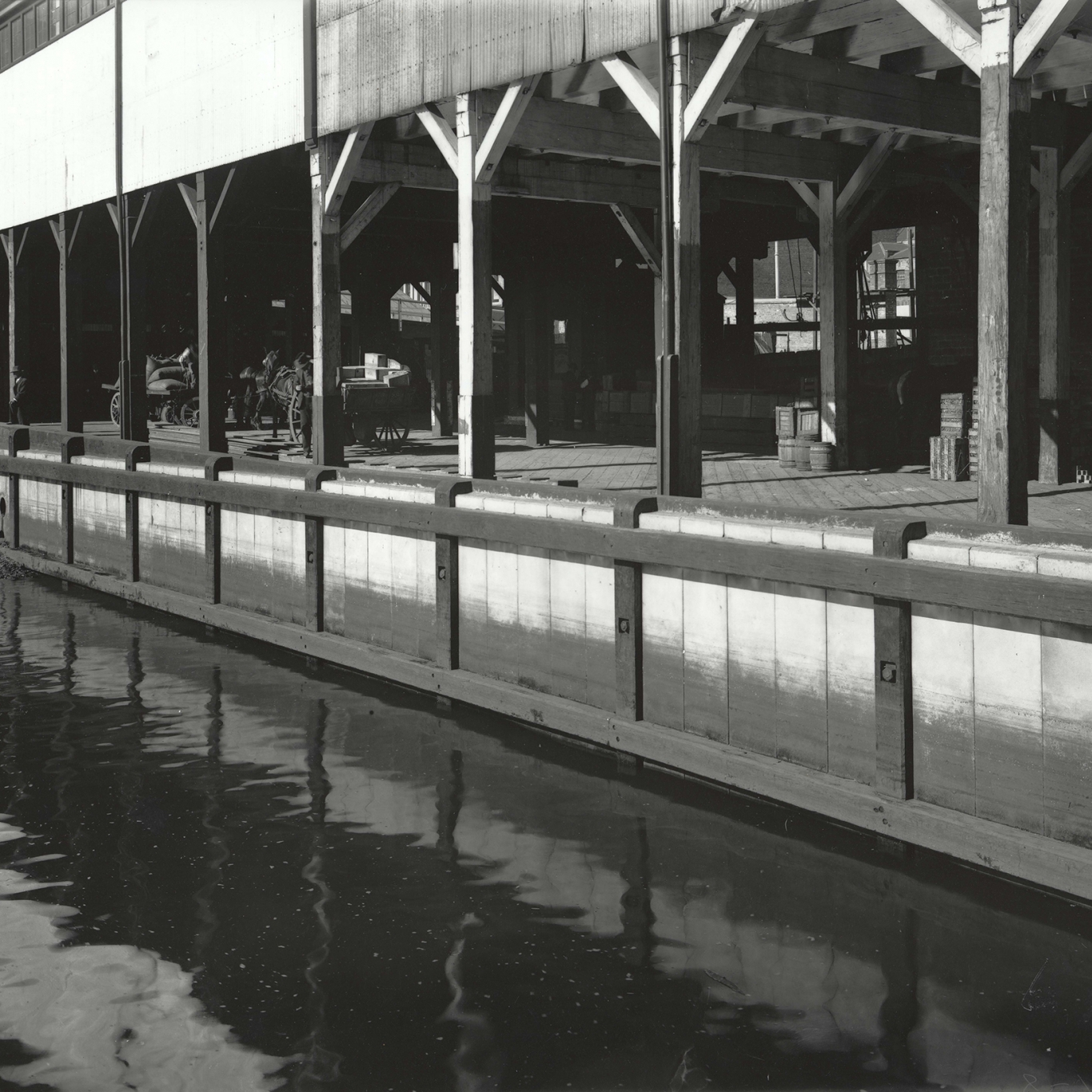 Black and white photograph of arched front of wharf.