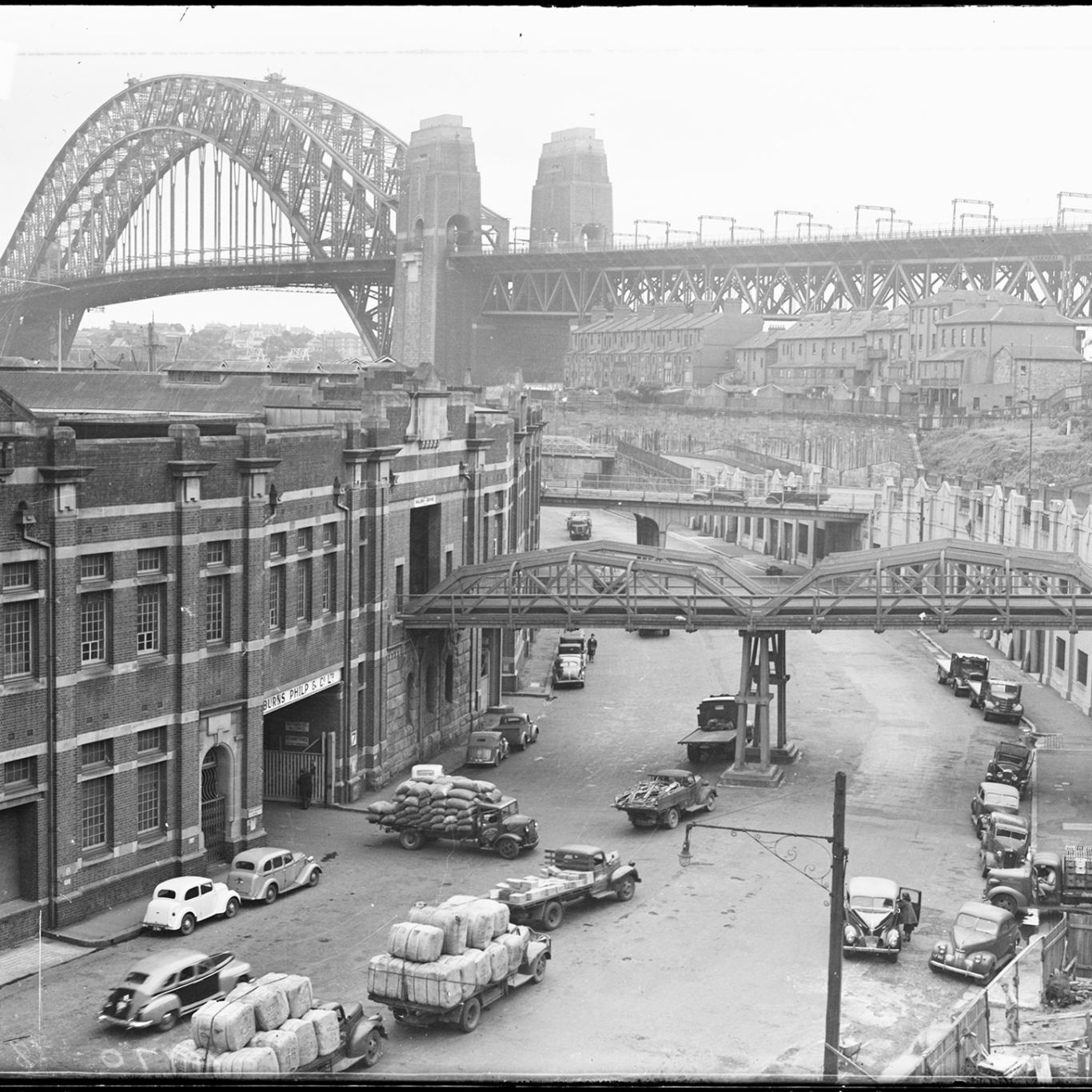 Black and white photograph looking along curved city street with Sydney Harbour Bridge in background.