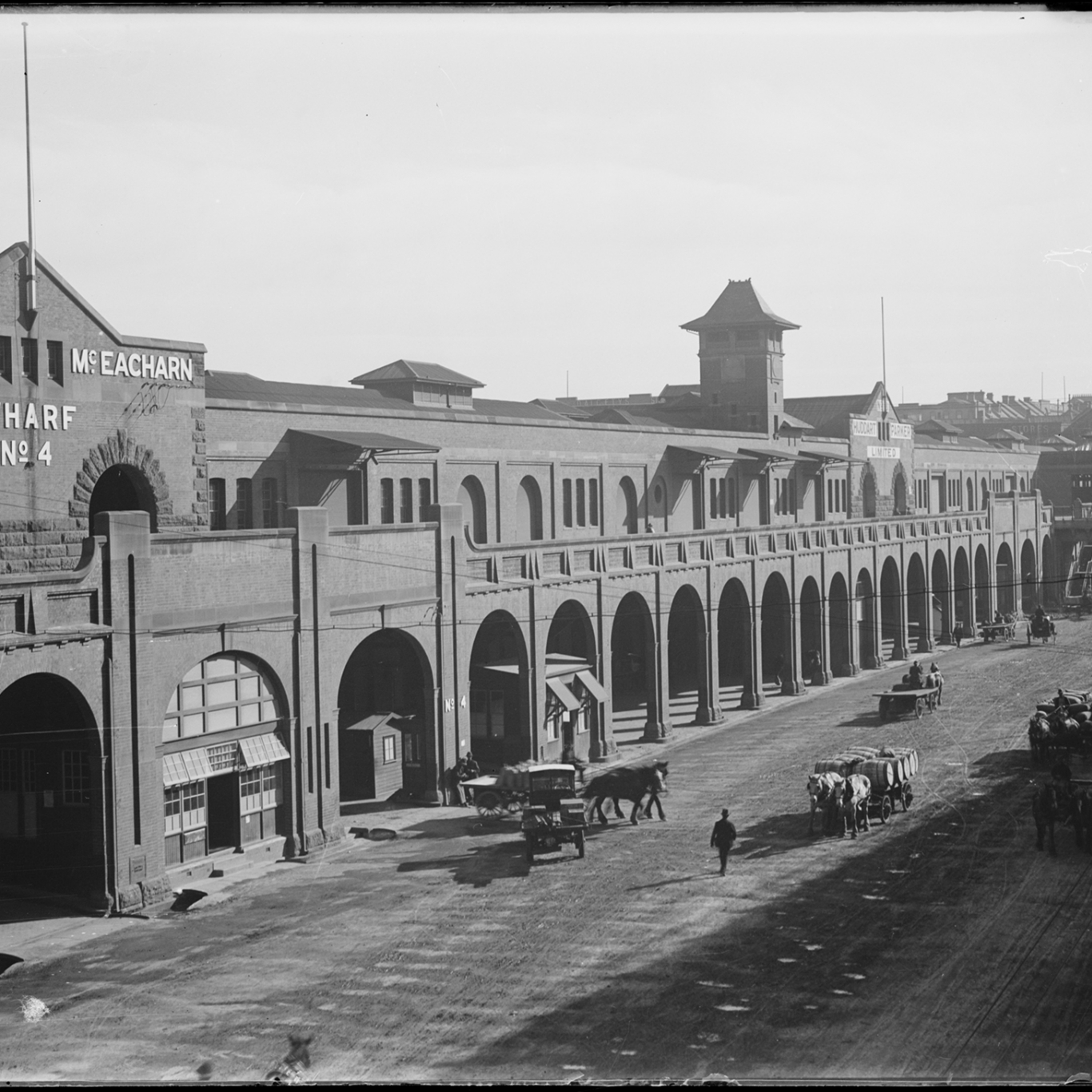 Black and white photograph looking along arched front of two storey wharf building.