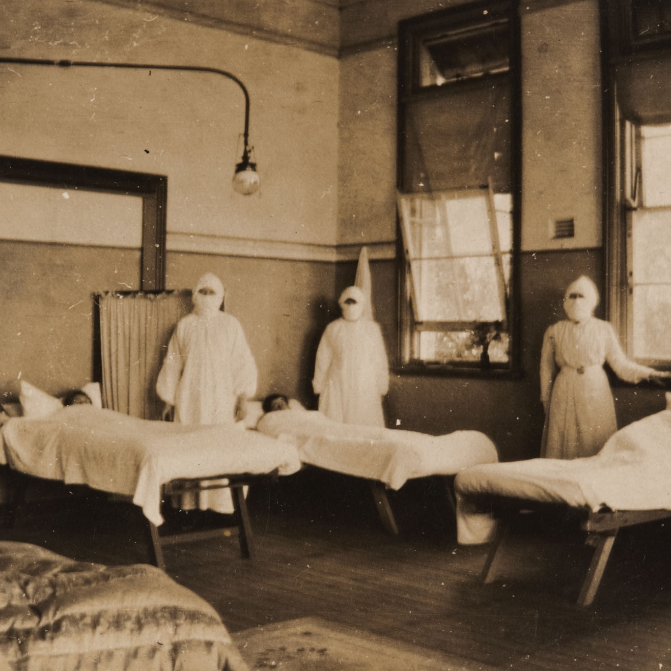 Four women in masks and nurse uniforms in room set up with hospital beds.