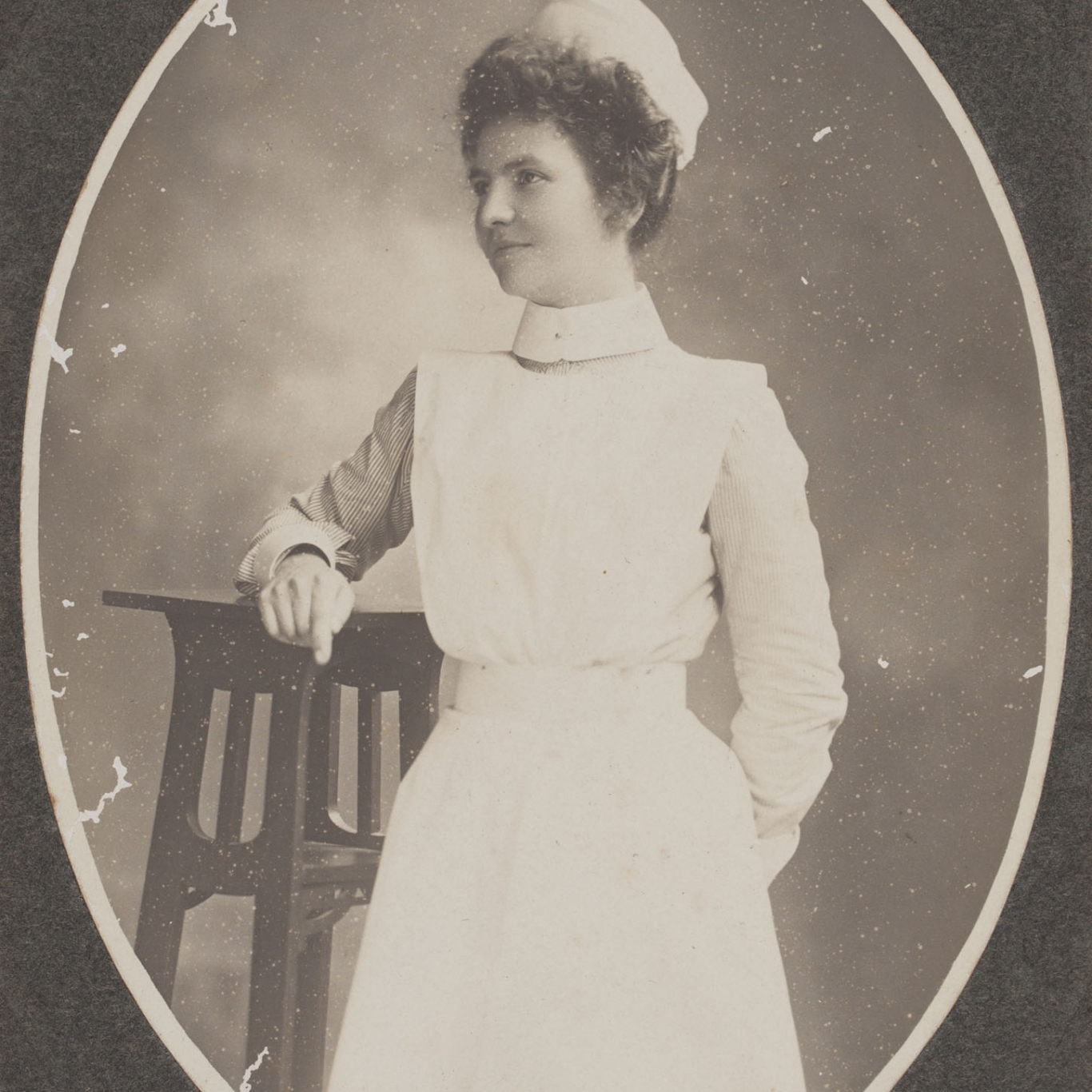 Cameo of woman in white uniform and cap.