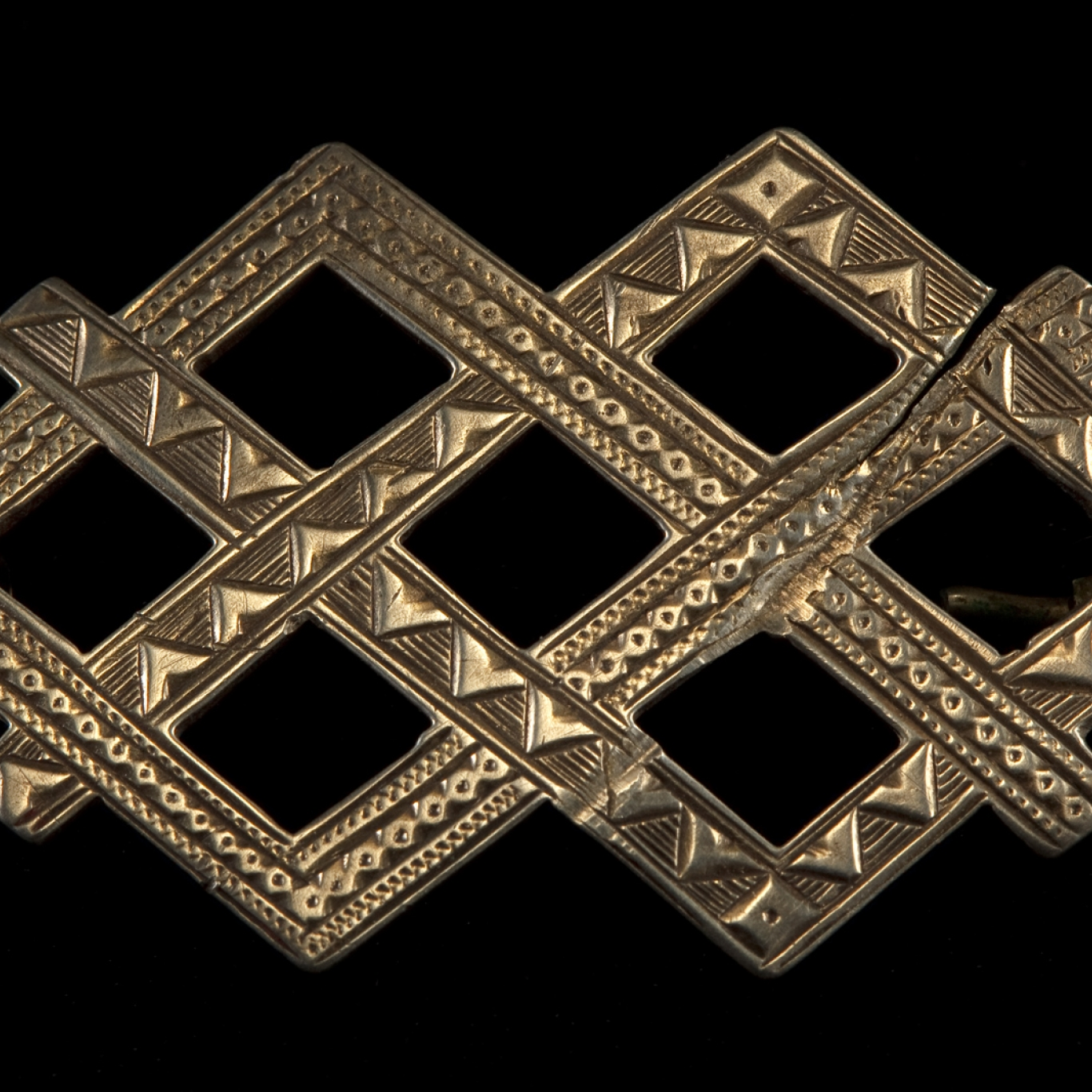 Silver/nickel brooch in the shape of 2 interlocking diamonds creating a lattice design with two contrasting surface textures - a chain pattern and a line of triangles.