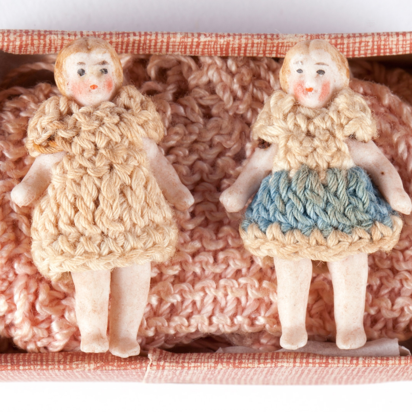 Two female dolls wearing crocheted clothing
