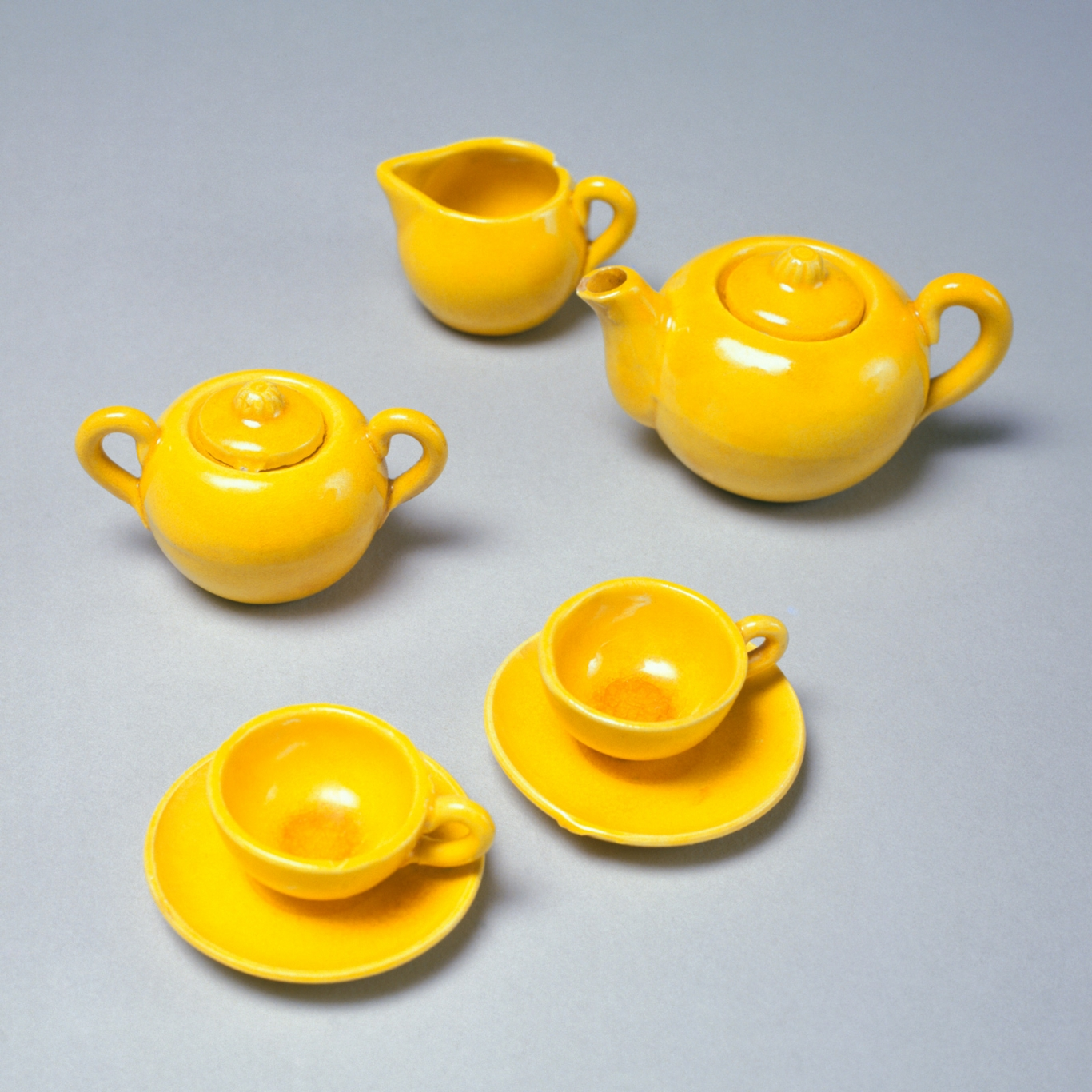 A stoneware teaset with a yellow glaze. The set has two teacups, two saucers, a lidded teapot, sugar bowl with lid, and a milk jug.