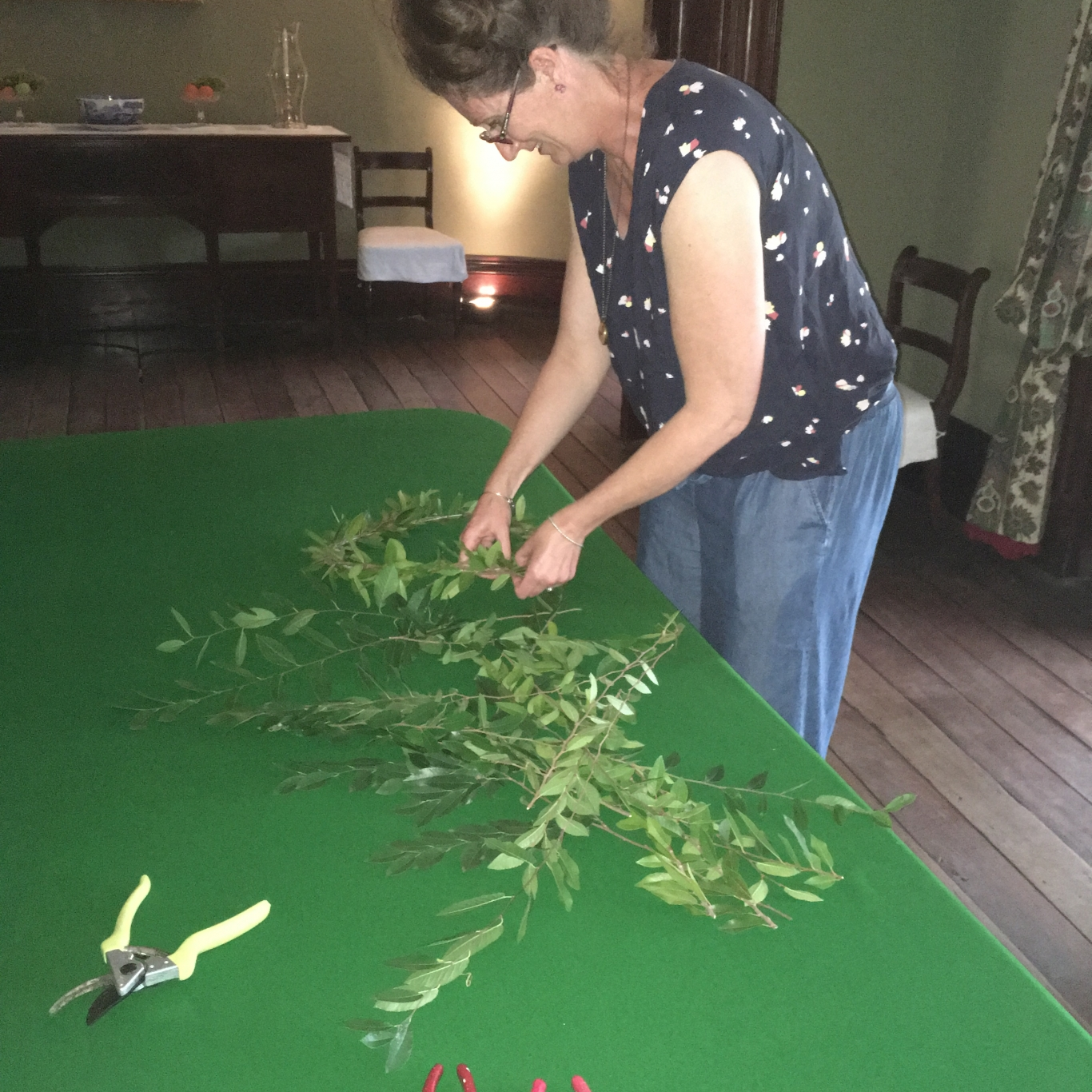 Woman preparing foliage on green topped table.