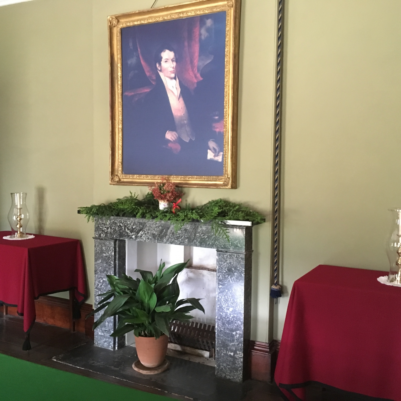 Floral decoration on mantelpiece with portrait above