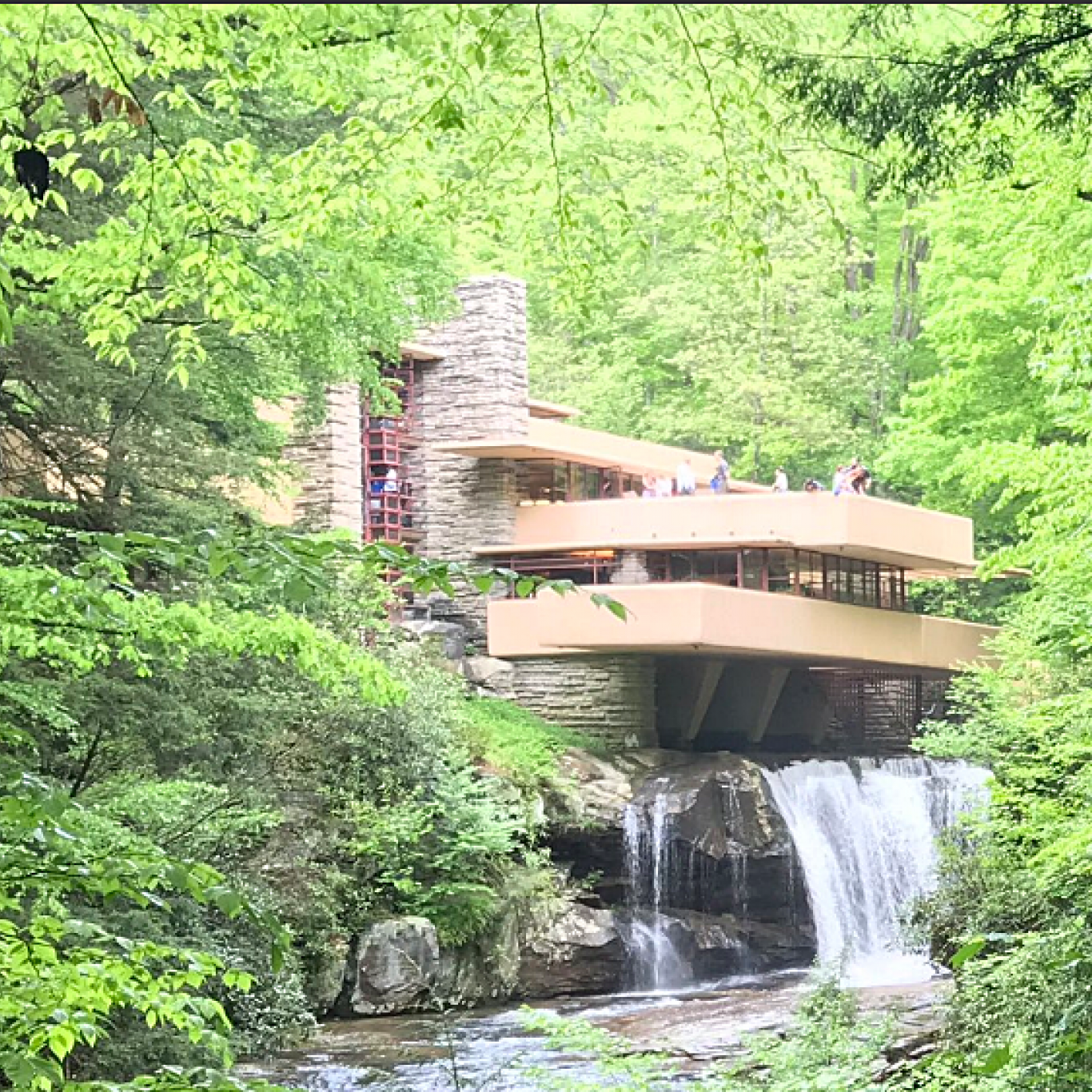 Modern house set in greenery with waterfall running into river.